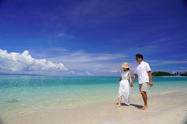 オクマプライベートビーチ&リゾート 手をつないでビーチを歩くカップル