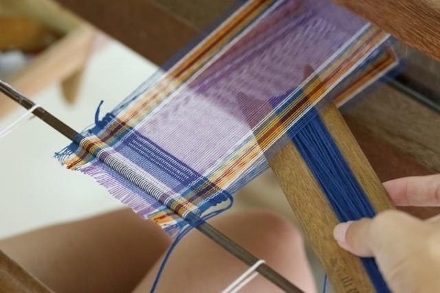 読谷村 伝統工芸品 グーシ花技法で機織りをしている様子